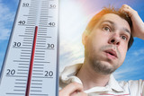 Hot weather concept. Young man is sweating. Thermometer is showing high temperature. Sun in background. - 202825317