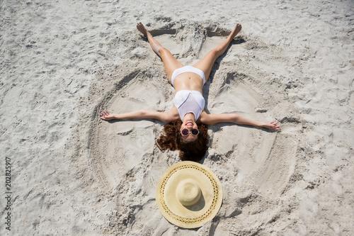 Fototapeta High angle view of woman making sand angel at beach