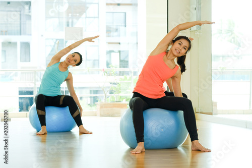 Poster Young asian women practicing yoga ball, fitness stretching flexibility pose, working out, healthy lifestyle, wellness, well being
