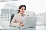 Happy businesswoman typing on laptop at her desk - 202845741