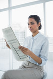 Softly smiling chic businesswoman reading newspaper  - 202847151