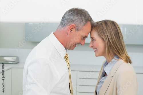 Side view of a happy business couple in kitchen