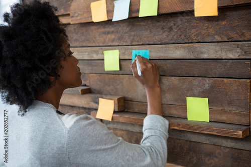 Foto Murales Female graphic designer looking at sticky notes