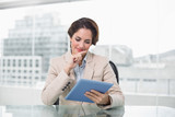 Businesswoman smiling and using her digital tablet - 202861779