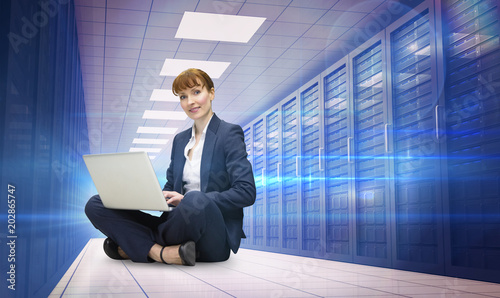 Businesswoman using laptop against server room with towers