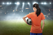 Young asian football player woman carrying the ball