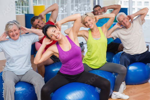 People on fitness balls exercising in gym class