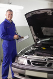 Smiling mechanic holding a clipboard and a pen - 202926968