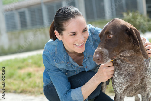 female vet stroking dog at animal shelter