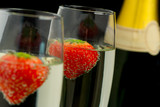 Strawberries floating in two champagne flutes - 202933130