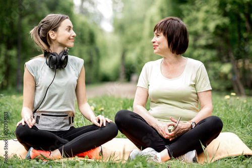 Poster Young and elder woman doing yoga in the park