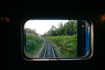 Train travel. Beautiful far scenic view through window from riding train at railway with nature ladnscape at sunset. Tourist trip. Atmospheric lifestyle journey. End of weekend. Farewell vacation.