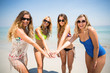 Young friends in bikinis stacking hands at beach