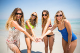 Young friends in bikinis stacking hands at beach - 202940125