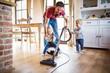 Leinwandbild Motiv Father and two toddlers doing housework.