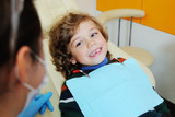 baby boy with curly red hair in blue dental chair. Children's dentist