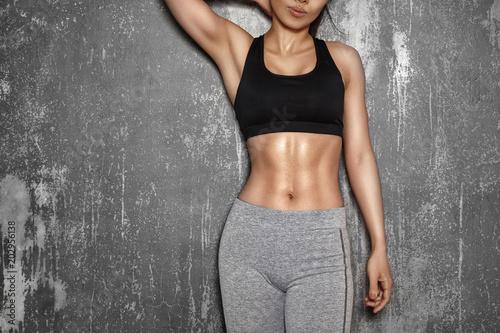 Fit Woman style with sexy hips. Kobieta z doskonałymi mięśniami brzucha. Piękny ciało w sport ubraniach blisko siwieje ścianę