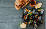 Mussels in garlic butter sauce served with parsley, toast and lemon - 202969724