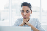 Concentrating businesswoman sitting at her desk  - 202971347