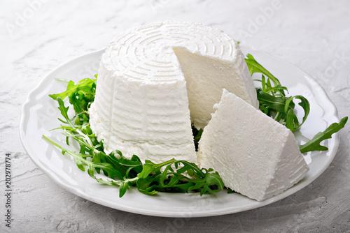 Fototapeta Ricotta cheese with arugula on plaster background
