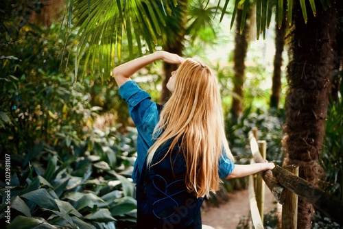 Fototapeta Girl tourist walking in the tropical forest