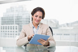 Businesswoman smiling and using her tablet pc - 202982761