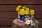 Mniszek lekarski w kolorowym wazonie na drewnianym tle - 202992954