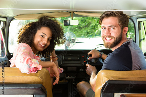 Wall mural Hipster couple driving in camper van