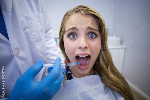Fototapeta Dentist giving anesthesia to female patient
