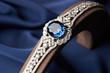 Close-up of a Beautiful platinum bracelet. Luxury women bracelet with diamonds and sapphire on blue silk background, close-up