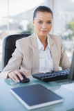 Serious businesswoman working on computer looking at camera - 203015924