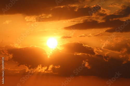 Plexiglas Rood traf. Golden sunset sky with dark fluffy floating clouds