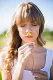 Pensive young woman smelling flower - 203020150
