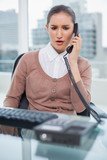 Furious businesswoman picking up the phone - 203021934