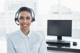 Attractive female agent wearing headset smiling at camera - 203027525