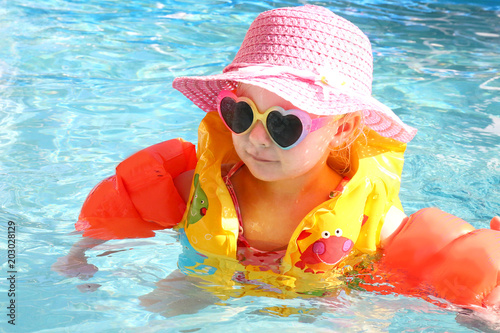 Little Toddler Girl Swimming in the Pool with Life Vest on a Sunny Summer Day
