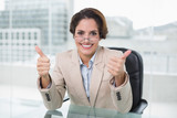 Happy businesswoman showing thumbs up at her desk - 203030747