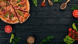 Pizza with sausage salami and mozzarella. Top view. On a wooden background. Copy space. - 203045169