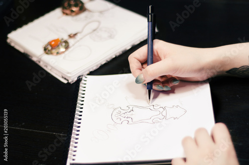 Artist designer girl draws a sketch of unusual jewelry ornaments with a pen on white paper. Home workshop © mellisandra