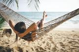 Happy woman relaxing in hammock - 203106390