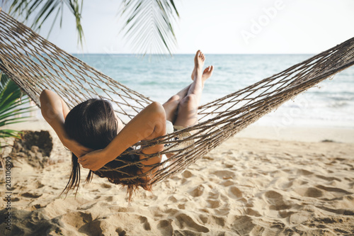 Leinwanddruck Bild Happy woman relaxing in hammock