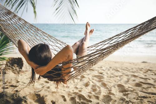 Leinwandbild Motiv Happy woman relaxing in hammock