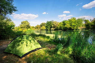 Green tent on the river bank