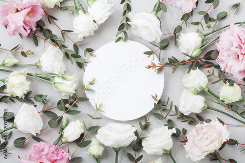 Beautiful floral mockup of pastel flowers and green eucalyptus leaves on grey table top view. Flat lay greeting card. - 203120193
