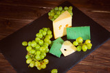 Shot of cheese and green grapes on black slate cheeseboard on wooden table