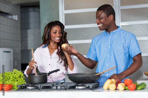 Wall mural Laughing african american love couple cooking at kitchen