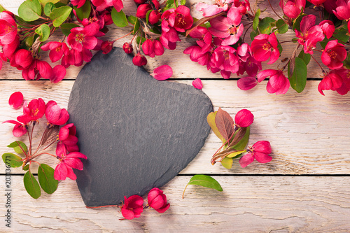 Fototapeta Herz aus Schiefer und Blüten auf Holz
