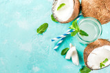 Healthy food concept.  Fresh Organic Coconut Water with coconuts, ice cubes and mint, on light blue background, copy space top view