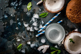 Healthy food concept.  Fresh Organic Coconut Water with coconuts, ice cubes and mint, on rusty dark blue background, copy space top view