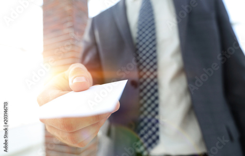Businessman giving a card. Close-up photo in loft office © FotolEdhar